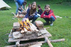 Junge Pfadfinderinnen kochen auf offenem Feuer